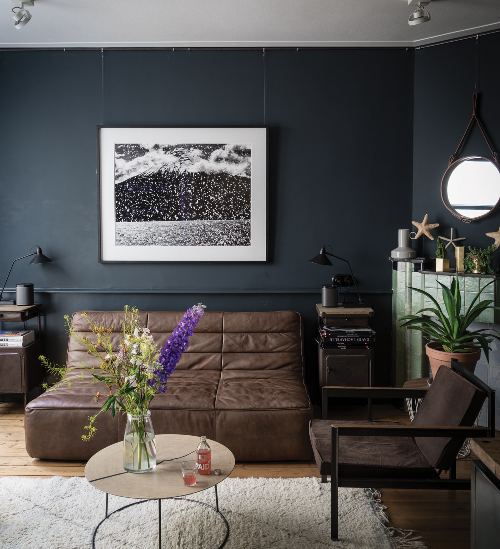 black living room with brown leather sofa and black lamps