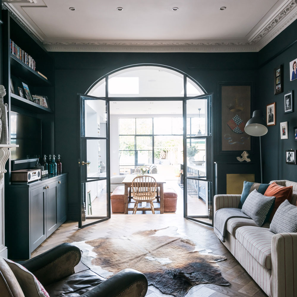 Black living room with arched glass doors leading to open plan dining and kitchen